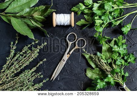 Bouquet garni. Classical french composition. Bay leaf parsley and thyme bound with culinary thread. Bunch of fresh aromatic herbs coil with threads old scissors on black textured background