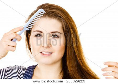 Woman combing her healthy hair using comb. Young latin female with beautiful natural brown straight long hairs studio shot isolated on white