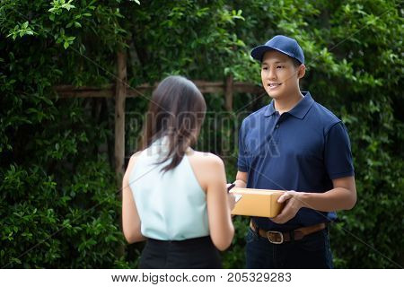 Young asian delivery man smiling while holding a cardboard box delivery to his customer.