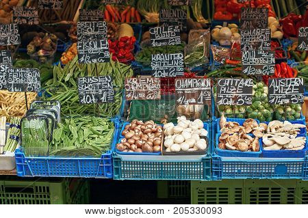 Raw food on the market display: scottish peas, green beans, champignons, shiitake mushrooms, oyster mushrooms, cabbage sprouts and other eatables.