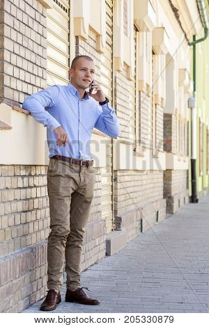 Young Handsome Businessman Standing In Front Of The Building And Talking On A Mobile Phone