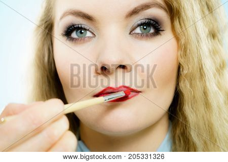 Professional make up artist applying on woman fashion model lips red lip gloss or lipstick using brush. Visage last touch concept.