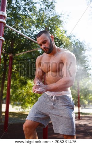 A muscular man is practicing on the street. The concept of a healthy lifestyle.