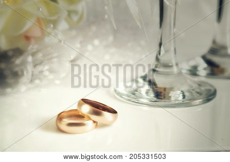 Gold wedding rings and wedding glasses on a light background. Blackout at the edges. Horizontal format. Indoors. Without people. Color. Toning. Photo.