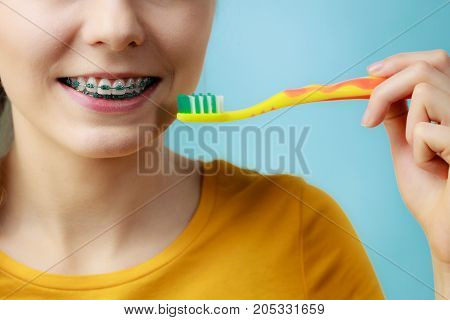 Woman With Teeth Braces Using Brush