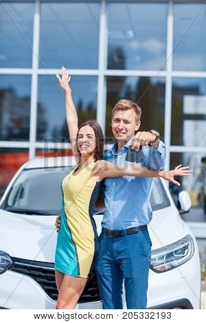 Proud owners. Beautiful young happy couple hugging standing near their newly bought car smiling joyfully showing car keys to the camera