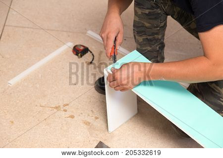 The worker works with plastic for windows in the house .