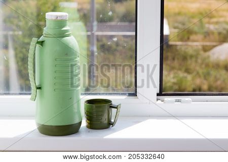 thermos with a glass on the window .