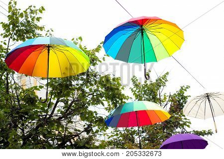 Bright umbrellas in festive decoration of city. Hanging multicolored umbrellas in sky above street. Avenue of flying umbrellas. Mood of joy and happiness
