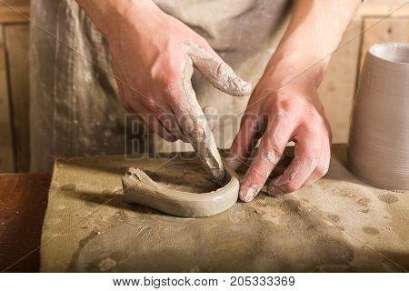 pottery, stoneware, ceramics art concept - closeup on craftsman fingers forming the handle from raw fireclay, master hands work with some piece of clay, male stand at a workshop near the table