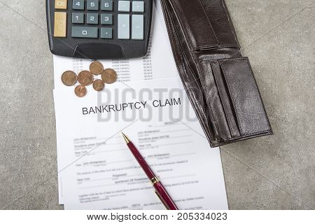 Bankruptcy concept image of a pen calculator and coins on financial documents.