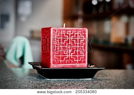 Big red square candle on the black plate with symetric pattern on front.