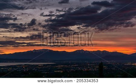 colorful sunset on top mountains in Utah above Orem and Provo cities