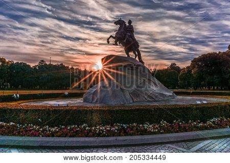 Dawn with light rays at the statue of Peter the Great at first light and dramatic clouds in St. Petersburg, Russia