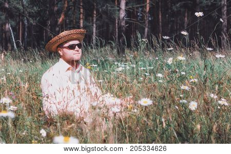 Bearded man in a straw hat and sunglasses rest among flowers on the forest lawn at sunny day. Selective focus vintage film filter.