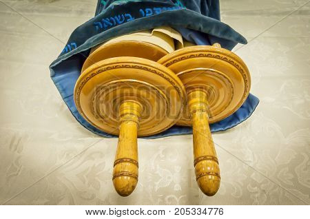 Classical Torah scrolls in a blue case with Hebrew letters. Torah is used in different religious services in a synagogue, especially during the holidays of the Jewish