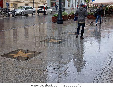 Wet street with stars. Lodz, Poland - September 20, 2017 Pedestrians on a wet sidewalk from the Star Cinema in Piotrkowska Street in Lodz.