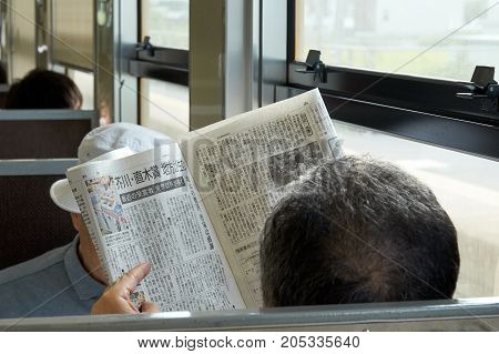 Yamaguchi City Japan - August 26 2017: An aging man is reading newspaper during in the train