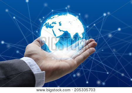 Businessman hand holding global network and global communication hand holding a glowing earth connected World.