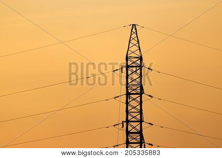 electric pole with wires on the golden sunset .
