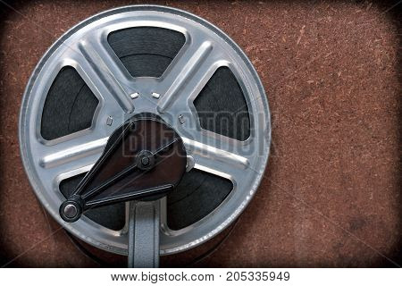 Coil with a film on a stand with a handle on a wooden background and a vignette