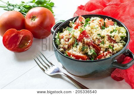 Bowl with couscous vegetables and herbs on pale gray background with red gauze napkin. Traditional food in cuisine of Maghreb. Vegetable ingredients: tomatoes and parsley. Dietary and healthy food