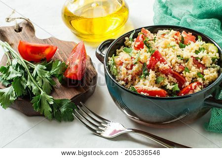Bowl with couscous vegetables and herbs on pale gray background with green gauze napkin. Traditional food in cuisine of Maghreb. Dietary and healthy food