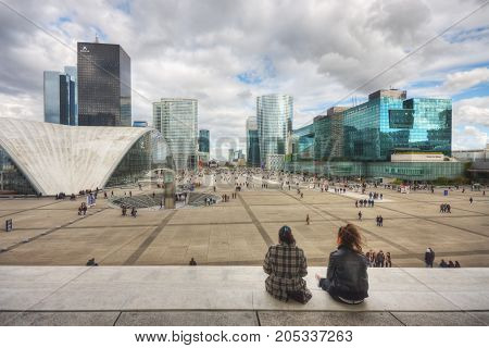 France, Paris - April 2008: Two girls are sitting on the steps of Grande Arche de la Defense and look to the Parvis de La Defense