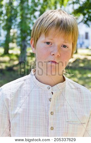 Portrait of serious boy in a white shirt in park