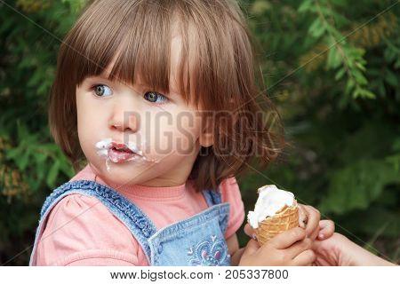 Photo of cute girl eating icecream in summer
