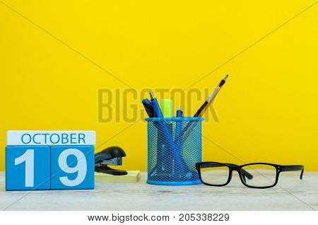 October 19th. Day 19 of october month, wooden color calendar on teacher or student table, yellow background . Autumn time.