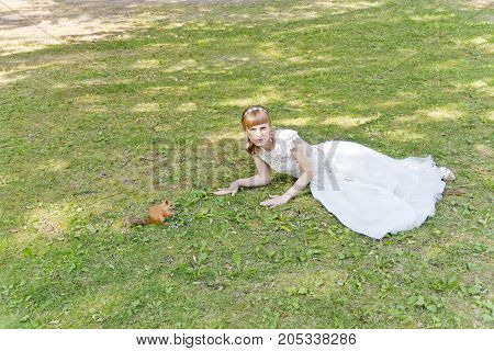 Bride in white lying on grass next to the squirrel in summer