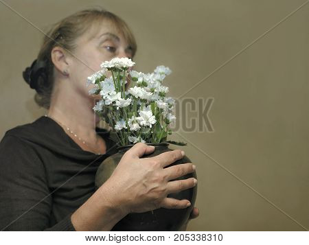 Woman holding a vase with beautiful chrysanthemum. Filterd studio portrait