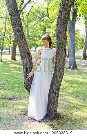 Bride in white lace dress standing near tree at the summer time