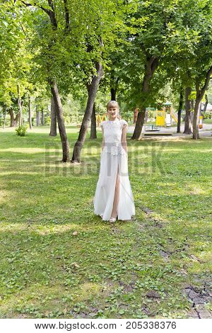 Bride in white lace dress walking in summer park