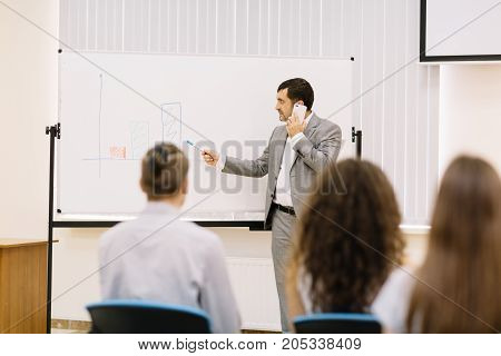Professional businessman talking on a phone on a blurred conference background. Corporate business meetup. Copy space.