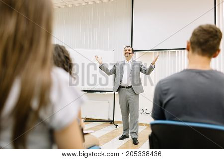 Happy and positive businessman in a suit giving a speech to young people on a blurred background. Students on a start-up conference.