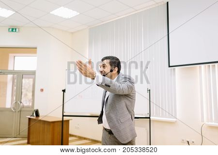 Professional businessman talking on a conference on a blurred office background. Corporate business meetup. Copy space.