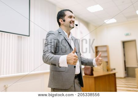 A successful business man showing thumbs up sign on the office background. Progressive and confident entrepreneur in a suit.