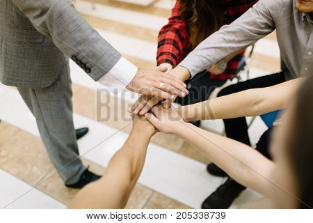 Close-up of young office workers holding hands on a light floor background. Top view of many hands showing unity and support.