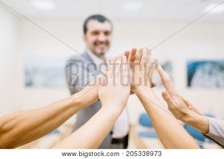 Close-up picture of many office workers showing unity with their hands on a blurred background. Business start-up project.