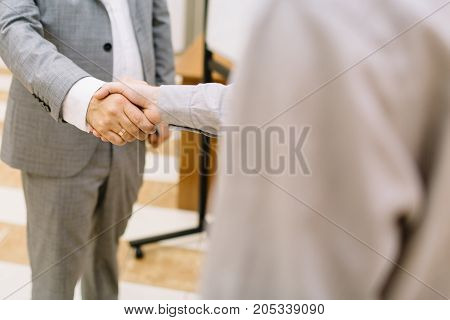 Close-up picture of two businessmen shaking hands on a blurred office background. Office workers making agreements close up.