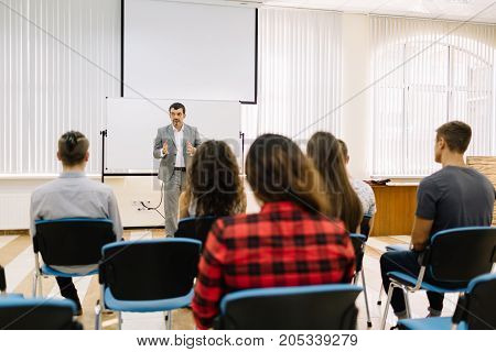 A mature, professional businessman speaking at the start-up meeting. Students listening to a business lecture on a conference room background.