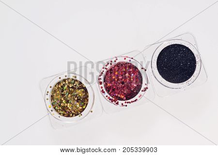 Black, red and golden glitters in transparent jars