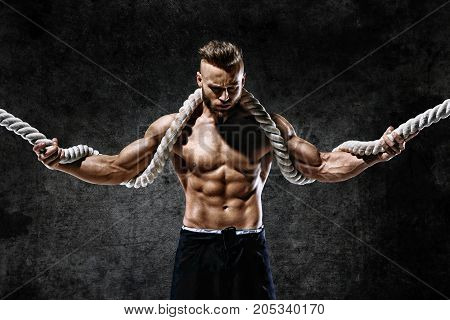 Athletic strong man with heavy ropes in hands. Photo of muscular male with naked torso on dark background. Strength and motivation