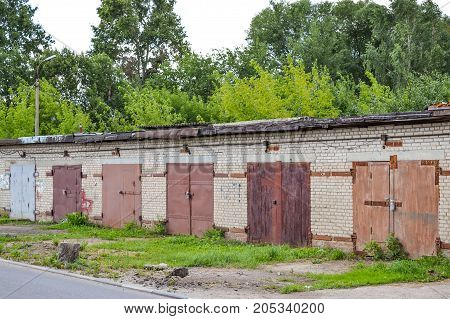 A row of brick garages with rusty metal gates. Russia