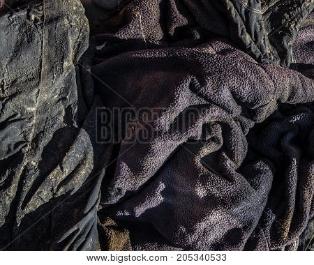 Grunge material. Grunge fabric. Fragment of an old dirty jacket. Grunge background. Grunge style. Grunge clothes. Grunge cloth.