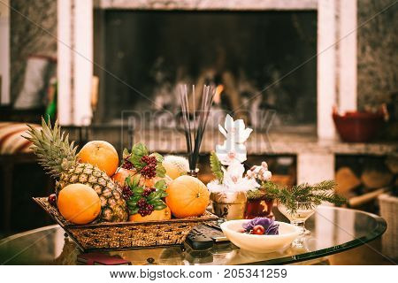 Cozy warm atmosphere inside living room with fireplace fruits and flowers on the table.