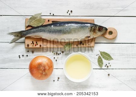 Herring with onions, vegetable oil and spices on a wooden board. The background. Rustic style, selective focus.