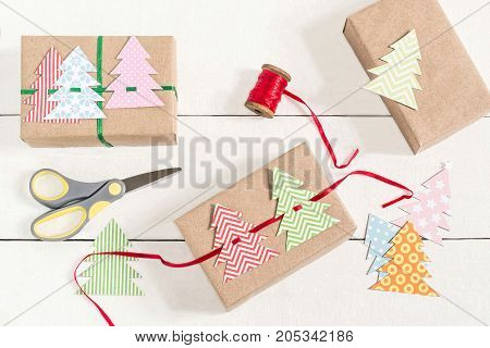 Making gift boxes for Christmas with your own hands. DIY hobby. Boxes are wrapped in kraft paper tied with ribbons with homemade colorful Christmas trees. Original gift decoration